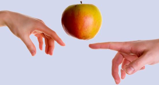 Foto artistica di due mani che sfiorano una mela con un dito