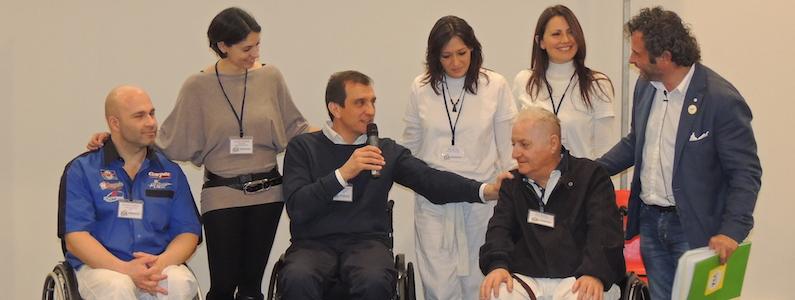 Gruppo di persone tra cui tre in sedia a rotelle parlano insieme durante una conferenza