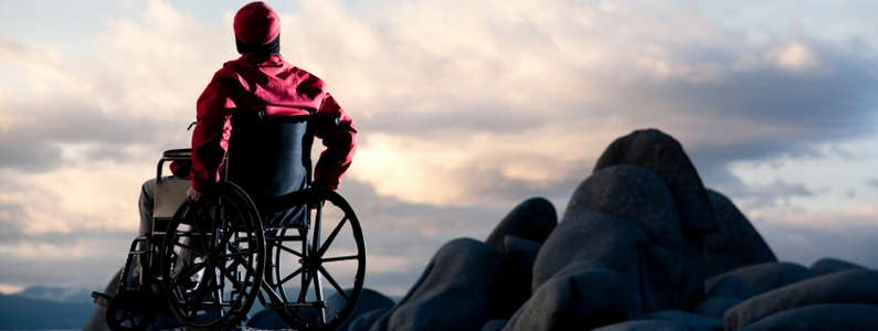 Persona amputata su sedia a rotelle che guarda l'orizzonte dagli scogli