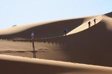 Quattro escursionisti percorrono una cresta di dune di sabbia finissima