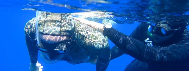 Istruttore guida persona con disabilità che nuota sotto la superficie dell'acqua