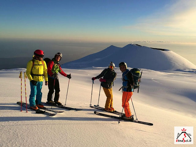 Sciatori si riposano in un paesaggio innevato al tramonto