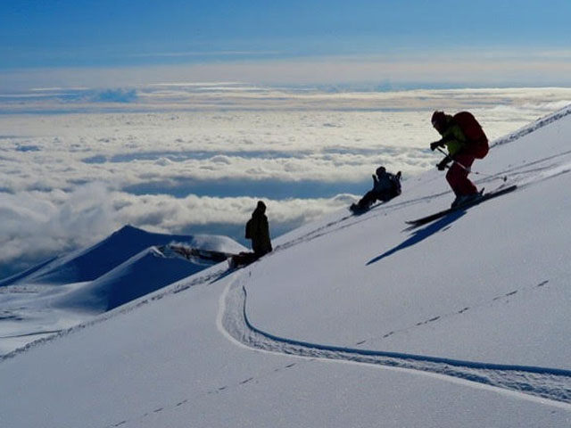 Sciatori scendono lungo una pista e sullo sfondo c'è un panorama mozzafiato