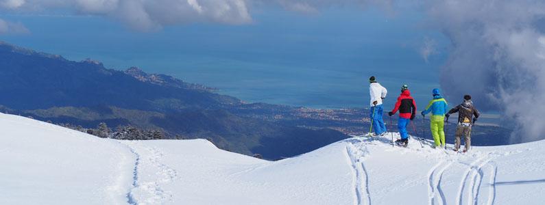 Sciatori fermi sul ciglio intenti a guardare il panorama