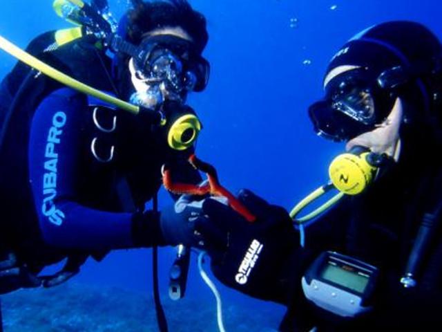 Due sub si passano un attrezzo mentre sono in fondo al mare
