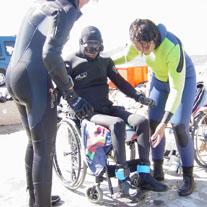 Claudio con la muta da sub seduto sulla carrozzina, in procinto di immergersi