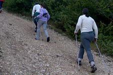 tre persone camminano in salita con bastoni da nordic walking