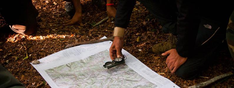 persone in un bosco con una cartina e una bussola