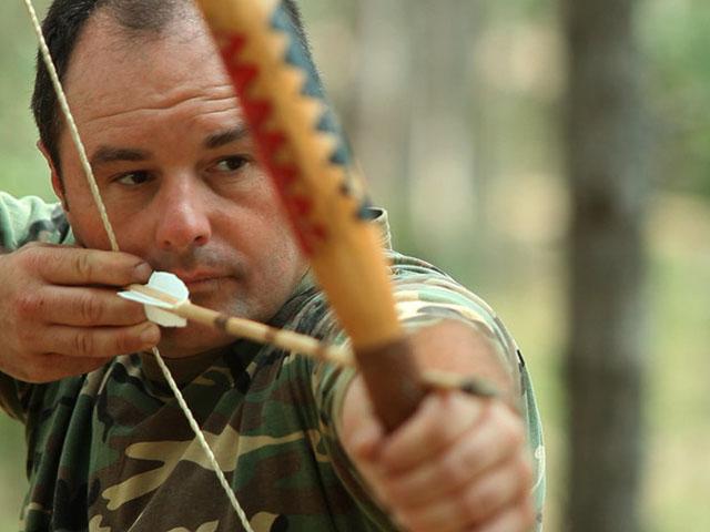 Primo piano dell'arciere mentre si prepara a scoccare la freccia