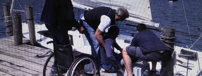Un ragazzo disabile viene sistemato dalla sedia a rotelle alla barca a vela
