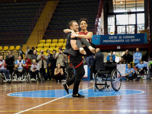 Coppia di ballerini con sedia a rotelle sullo sfondo