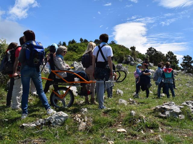 Gruppo di persone disabili e non attraversano un tratto in montagna