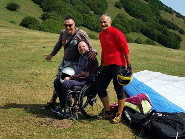 Disabile in carrozzina con gli istruttori accanto al deltaplano