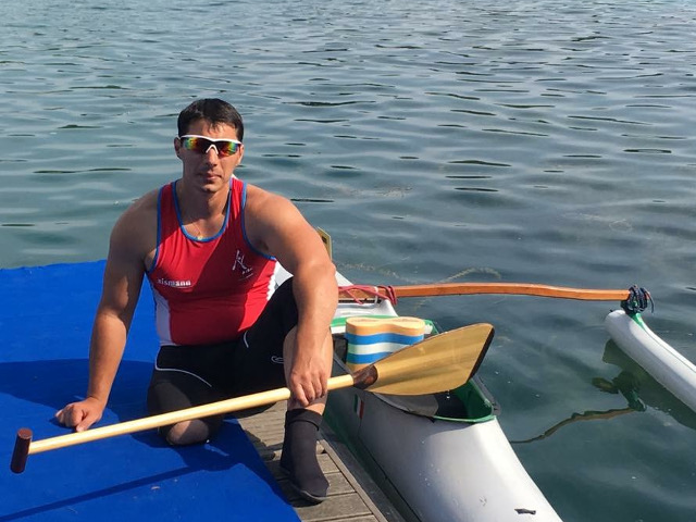Sportivo seduto sul molo accanto alla canoa
