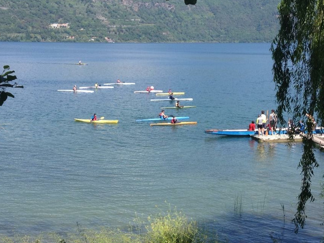 Numerose canoe salpate dal molo nell'incantevole cornice del Lago di Castel Gandolfo