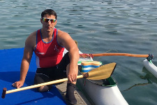 Atleta in posa accanto alla sua canoa