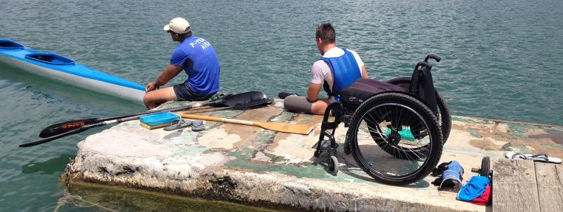 Carrozzina lasciata al molo mentre due sportivi sono in procinto di salire in canoa