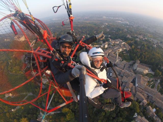 Il pilota e un'anziana signora salutano la fotocamera mentre sono in volo con il parapendio