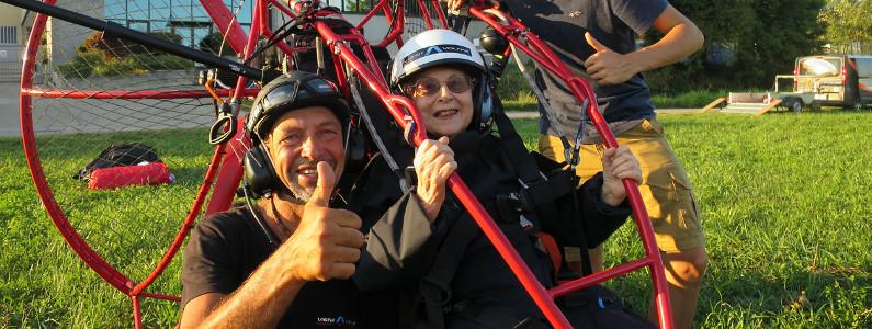 Il pilota e un'anziana signora salutano la fotocamera prima di elevarsi con il parapendio