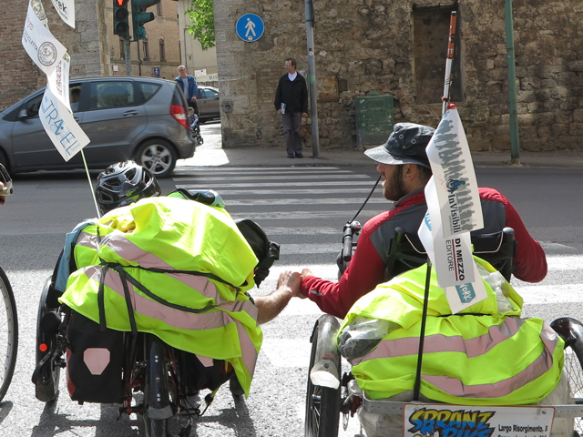 Due disabili su hand-bike in un punto cittadino del tragitto