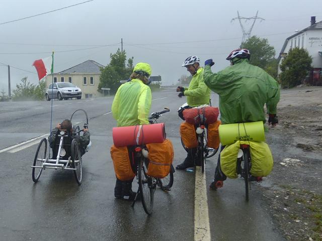 Pellegrini su due ruote sotto la pioggia