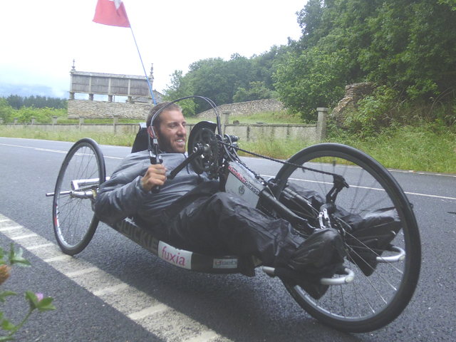 Persona con disabilità sul cammino con il proprio speciale mezzo a tre ruote
