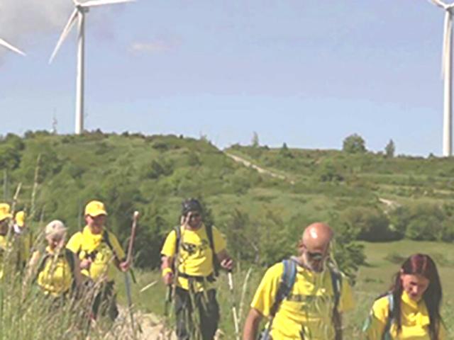 Gruppo di escursionisti con pale eoliche sullo sfondo