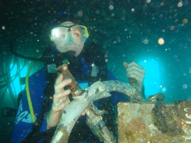 Una subacquea durante un'immersione tiene il timone di un relitto