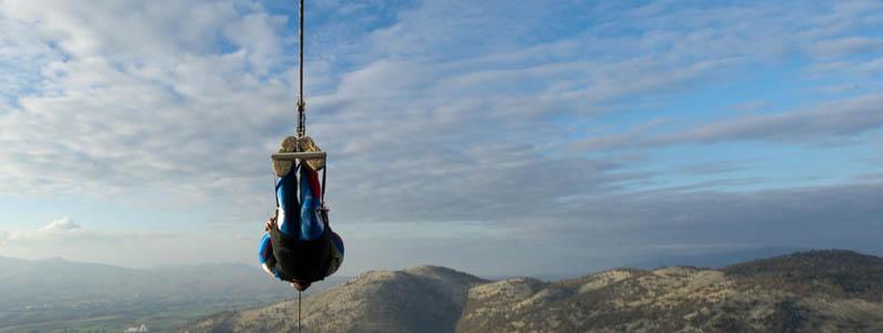 vista panoramica della scuola di sci con alle spalle montagne e pini innevati