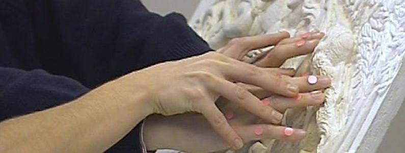 """La mano del visitatore """"guarda"""" l'opera a rilievo"""