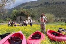 Escursionisti su un prato con in primo piano le loro canoe attraccate