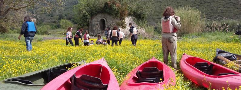Canoe lasciate sull'argine del fiume, sullo sfondo gli escursionisti proseguono a piedi
