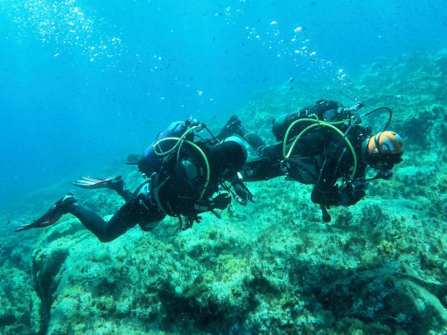 Due sub esplorano un fondale di scogli