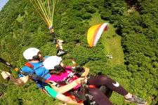 Foto scattata dall'alto che riprende una ragazza con l'istruttore durante il volo in parapendio