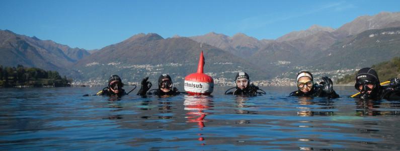 Gruppo di sub in acqua in procinto di immergersi nelle acque del lago