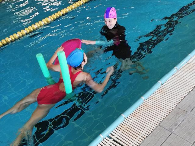 Una ragazza disabile in piscina durante la sua lezione di nuoto