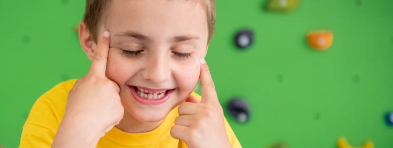 Un bambino sorride ad occhi chiusi e sullo sfondo c'è la parete da arrampicata
