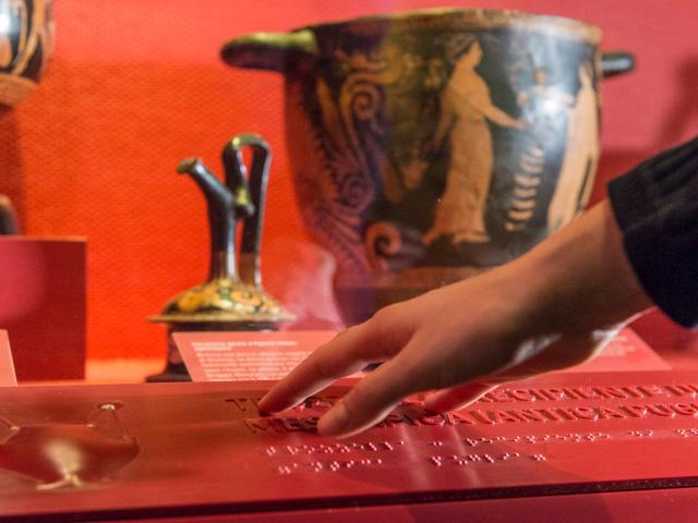 Una mano legge attraverso il tatto le didascalie a rilievo ed in braille di alcuni vasi antichi