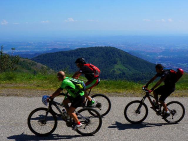 Tre ciclisti su strada con panorama sullo sfondo