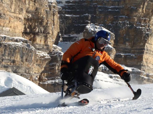 Sciatore seduto su monosci durante una discesa