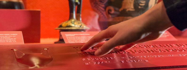 Una mano legge attraverso il tatto le didascalie a rilievo ed in braille delle opere