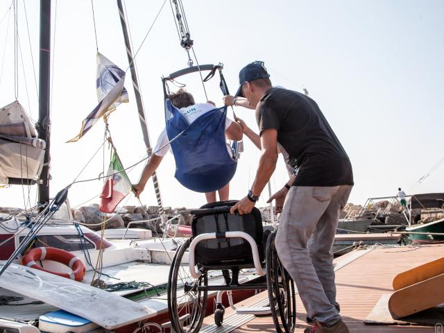 Un velista con disabilità motoria si cala con un apposito imbrago nella barca a vela