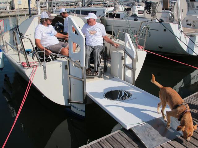 Due velisti con disabilità sono all'interno della loro barca a vela ormeggiata in porto, pronti per scendere