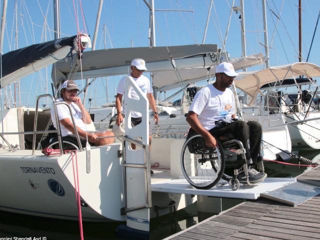 Un velista con disabilità scende dalla barca con la sua sedia a rotelle utilizzando una passerella