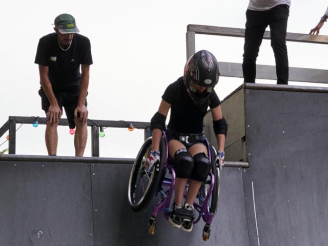 Una ragazza in sedia a rotelle scende il muro verticale