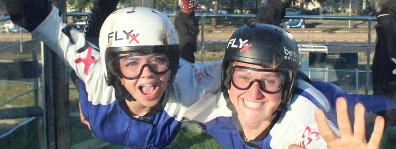 Due ragazze sorridono sospese nella galleria del vento